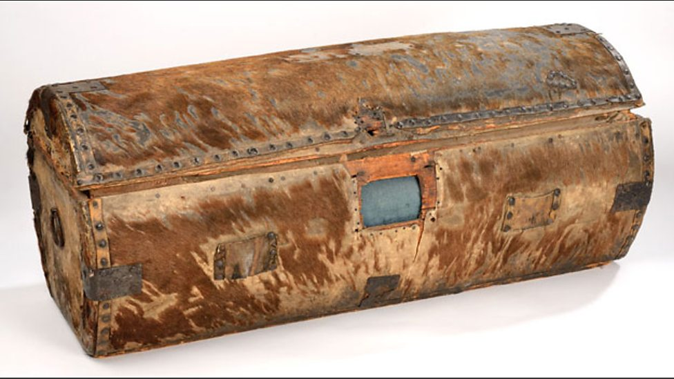 A brown rectangular trunk with curved lid and metal studs along the edges