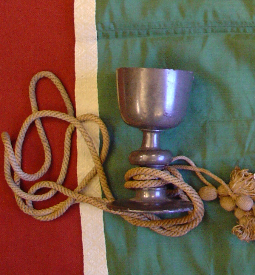 A chalice with a rope tied around the stem lying on green material