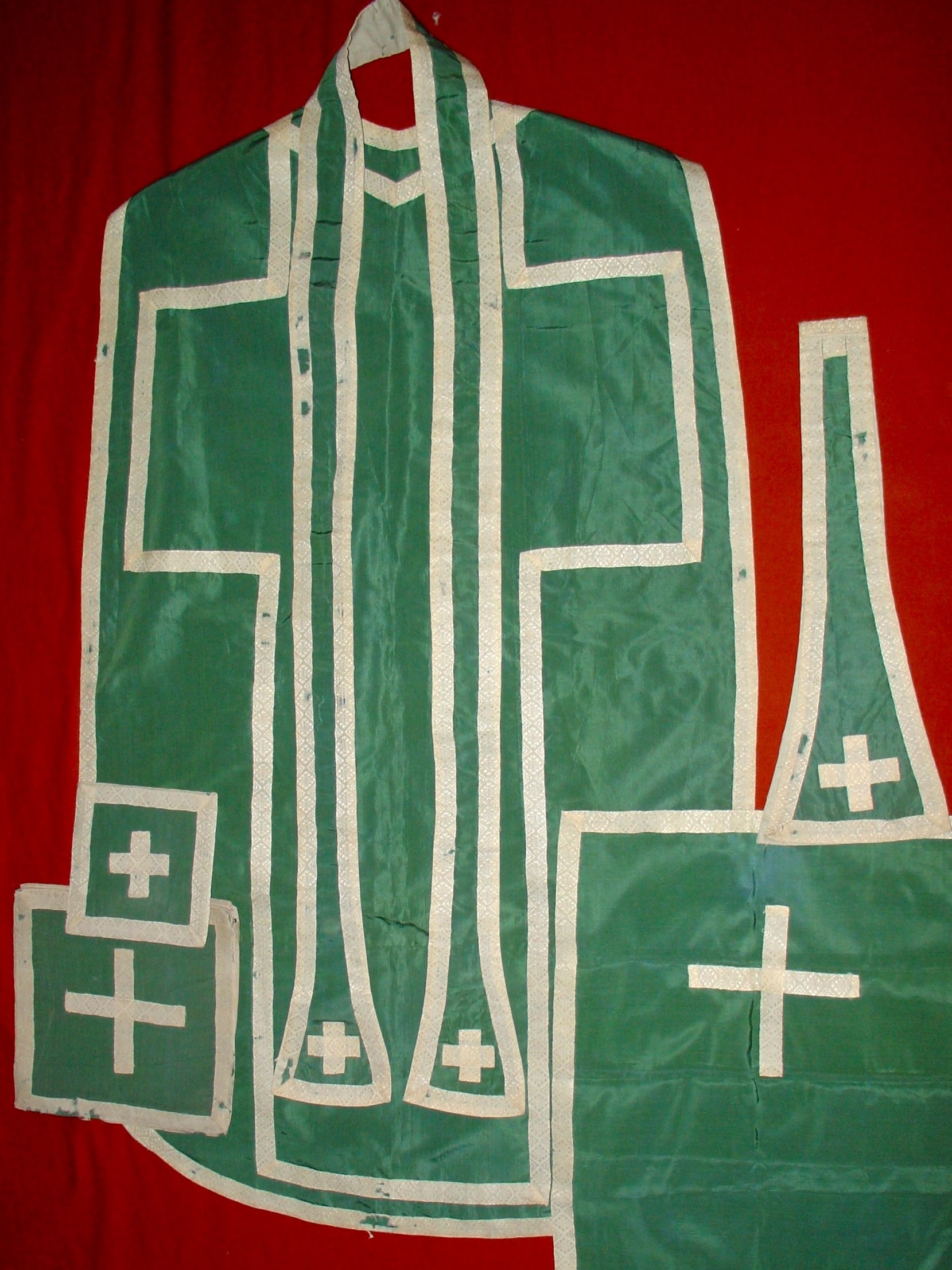 Green silk vestments which have been laid out on red cloth