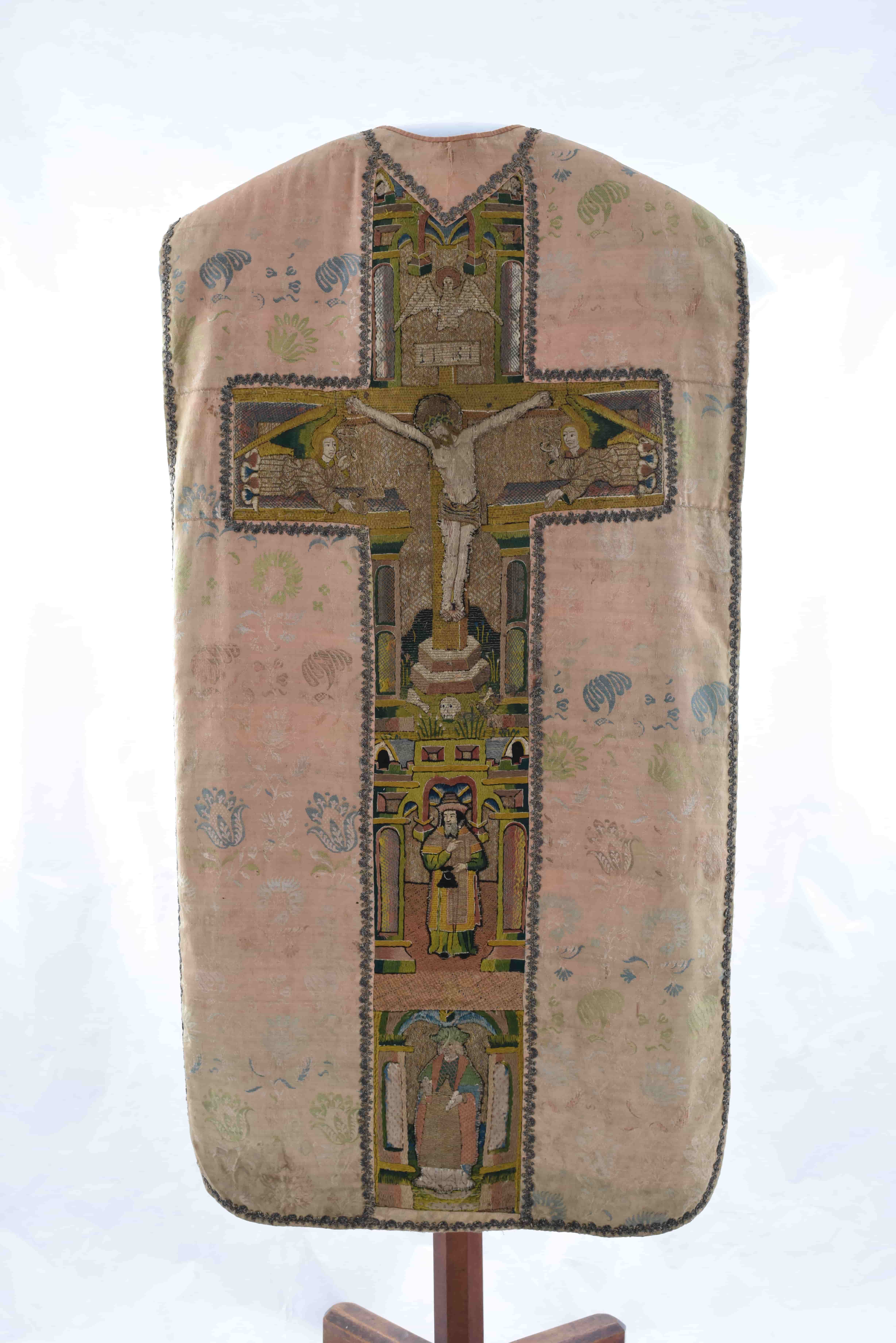 A vestment on a stand viewed from the back. The majority is made of a faded floral fabric and running down the length of the centre is a cross with an embroidered crucifixion scene