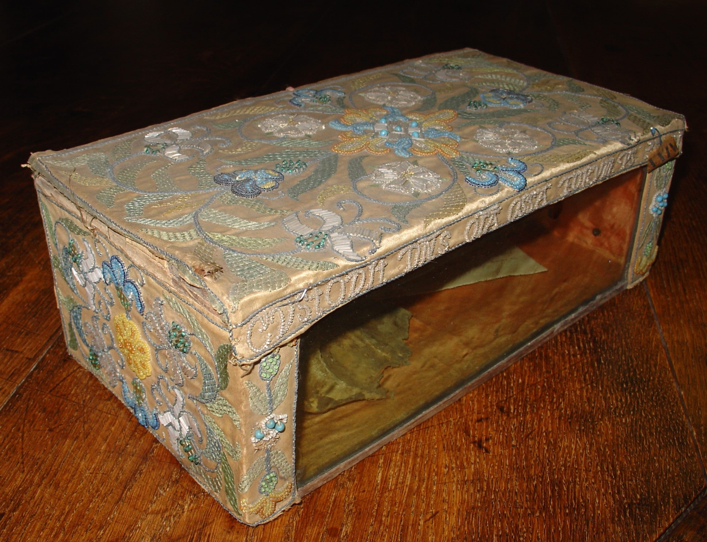 Embroidered chest sitting on a wooden floor with a glass panel on the side revealing a bone
