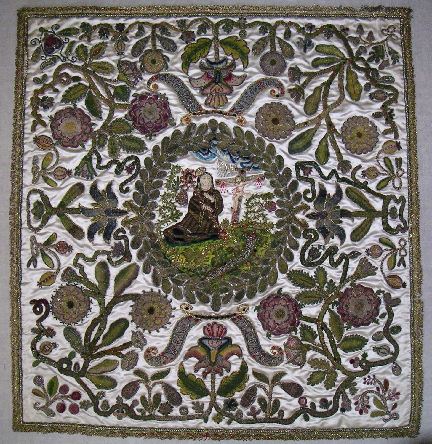 A square of material embroidered with floral motifs. In the centre, inside a circular wreath, is a seated white appearing woman gazing at Christ on the cross