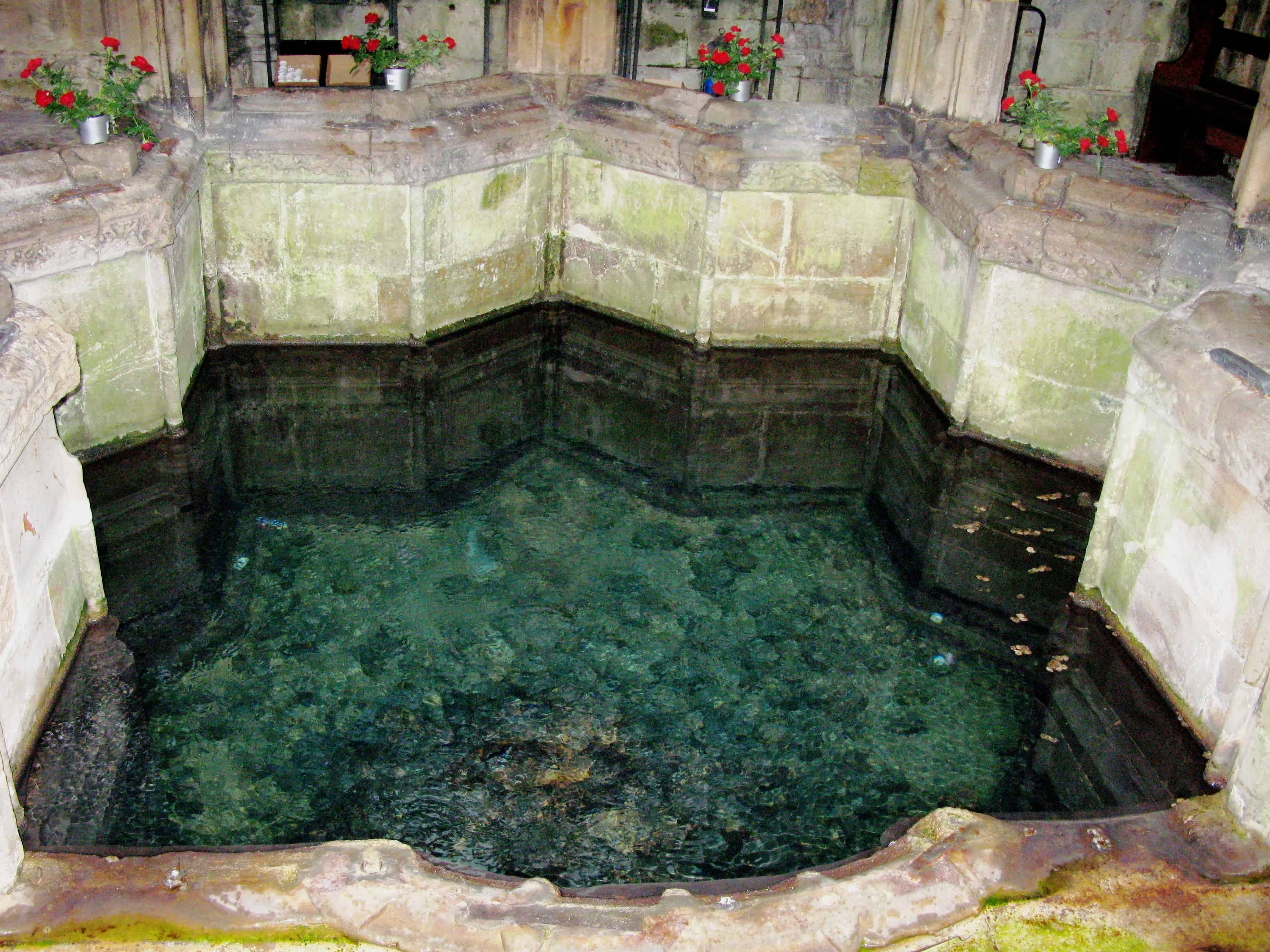 Photograph of turquoise water in star shaped stone well. Four vases of red flowers have been placed around the edge