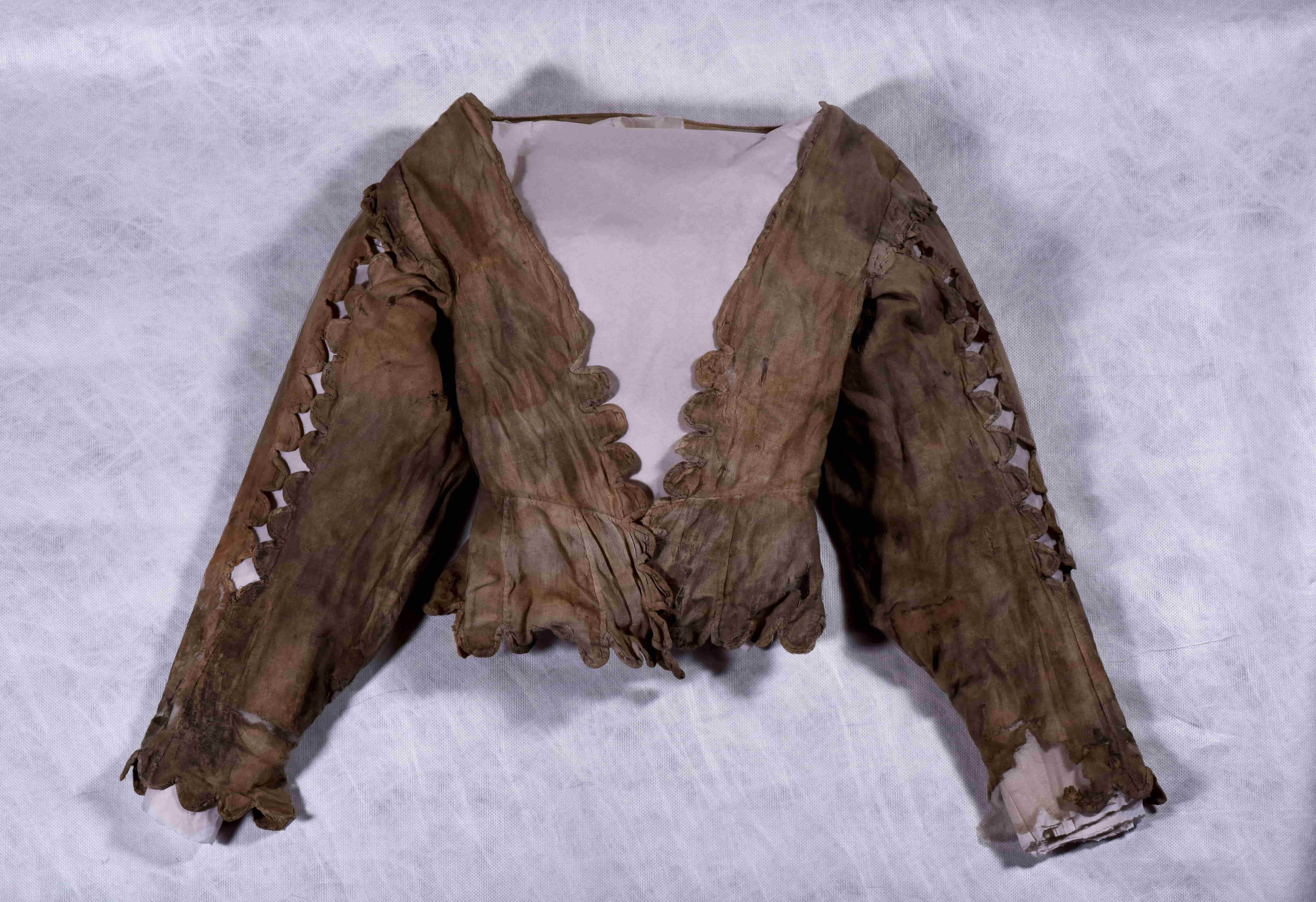 A woman's bodice with long sleeves. There are diamond-shaped cut-outs along the sleeves and scalloped edging to the cuffs, hem, and opening of the bodice