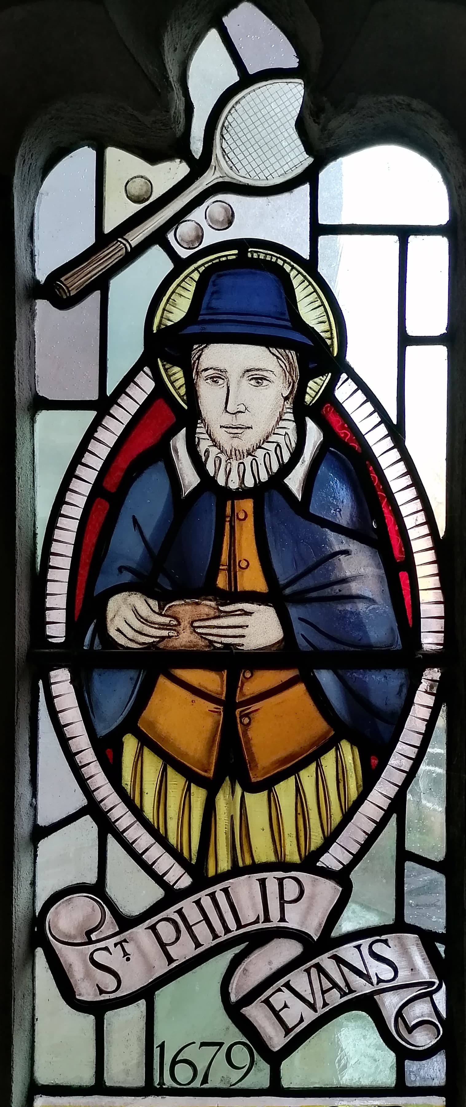 A portrait of a man in stained glass. He is wearing brown garments, a rough, a blue outer garment and a blue hat. Above his head is a tennis racket and three tennis balls. Underneath the figure is written St Philip Evans 16 79