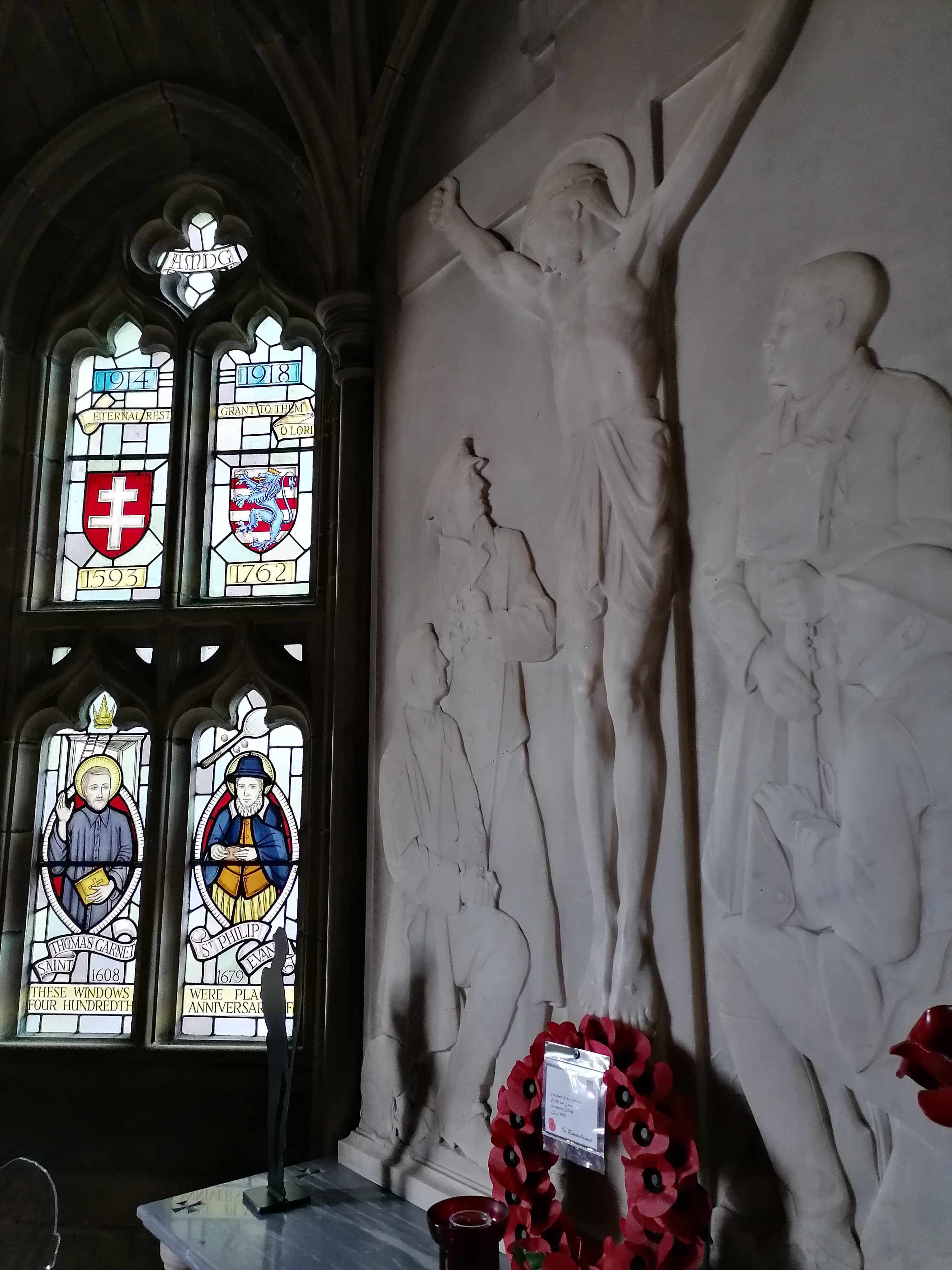 In the foreground of this photograph is a carved image of Jesus on the cross. Four men dressed as soldiers have been carved at the base of the cross looking up at Jesus. In the background is a stained glass window. Two figures, Thomas Garnet and Philip Evans, are depicted in the window