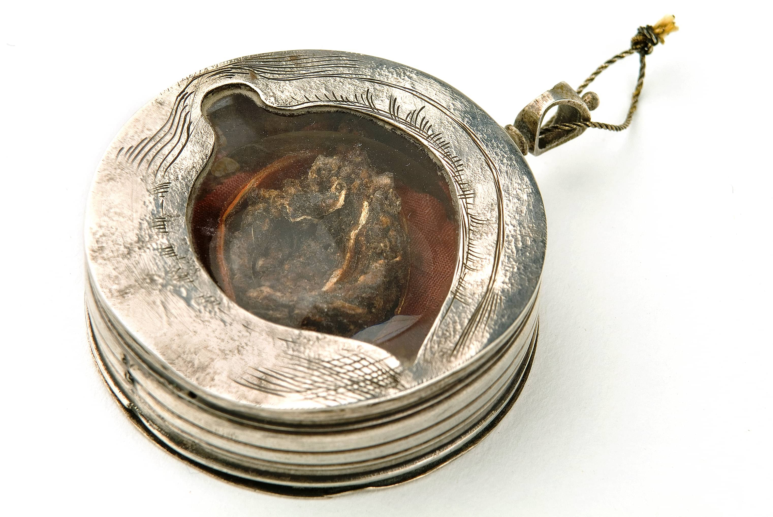 Photograph of a round silver container with a glass oval shaped top insert showing a grim looking shrivelled up object within. Around the glass the silver has been scored to look like eyelashes.