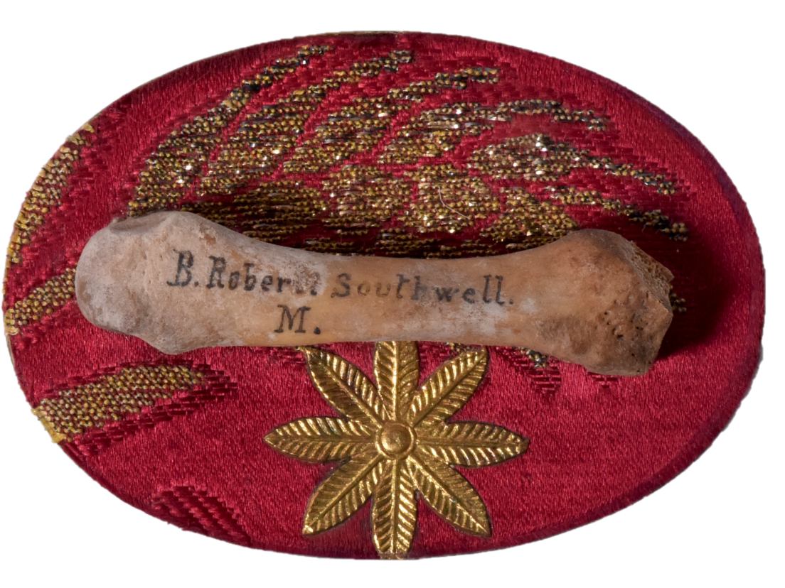 Small bone on red cloth with gold floral embroidery