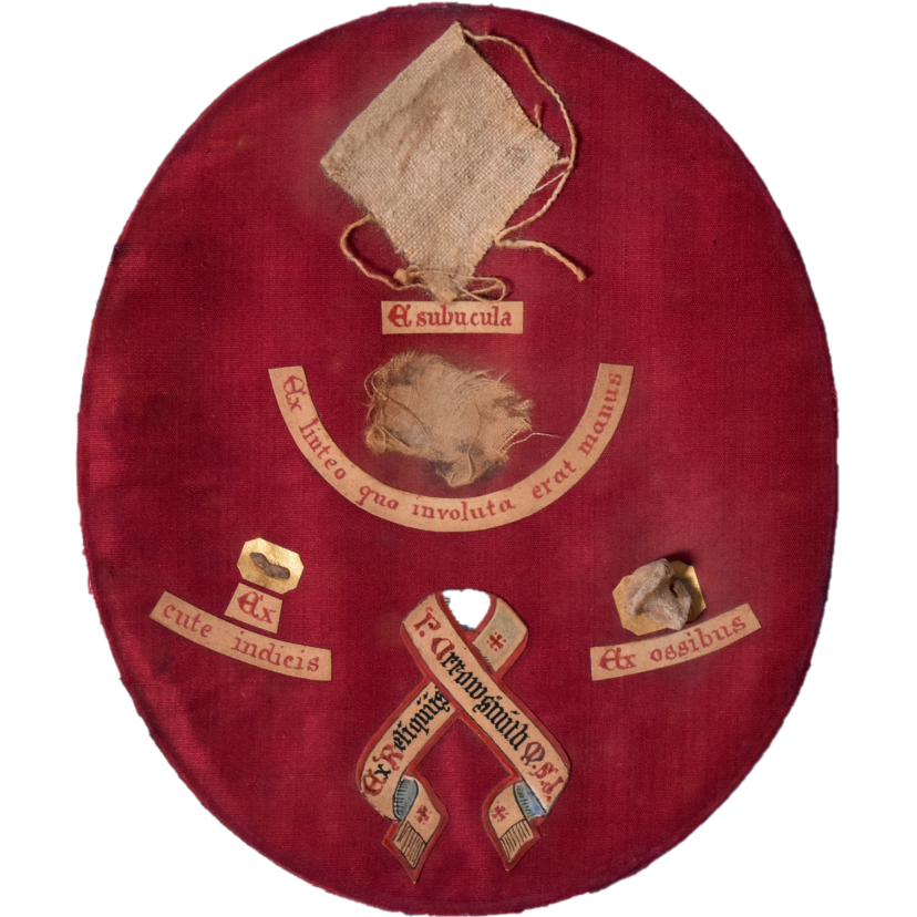 Four small relics on an oval of red cloth. There are handwritten labels in Latin to identify the relics