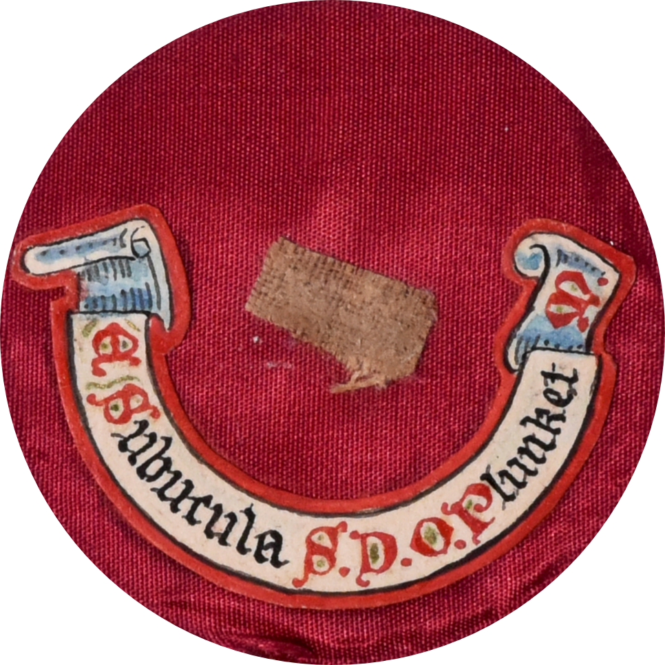 Small piece of linen, with a label underneath it illustrated to look like a scroll and an inscription in Latin, on a red circle of cloth