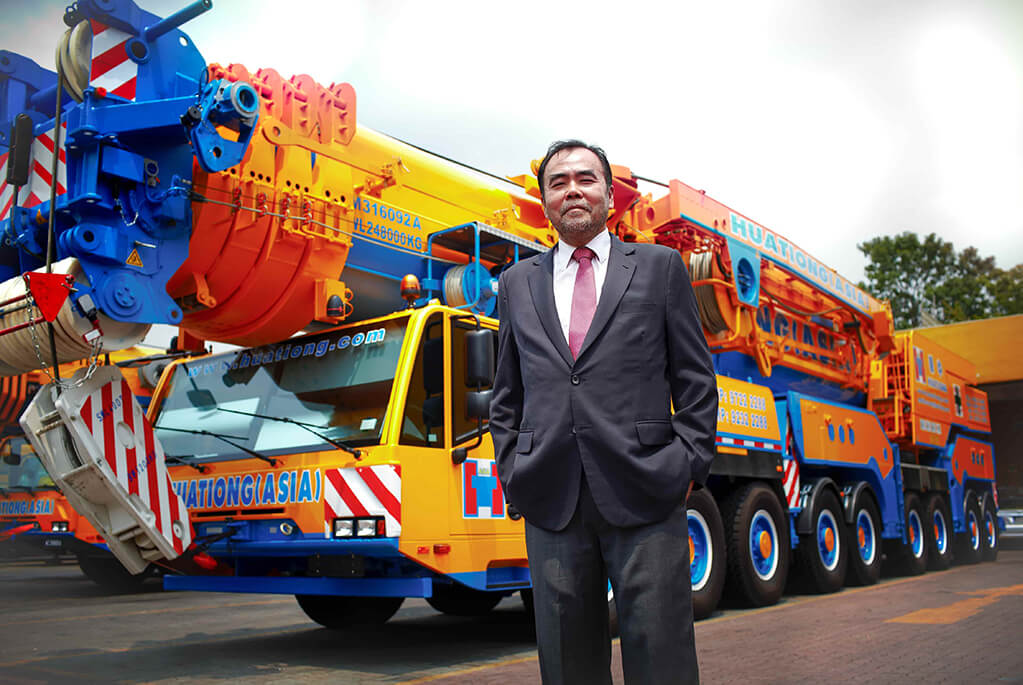 Jimmy Chua, the owner of Huationg Construction Singapore standing in front of a mobile hydraulic crane