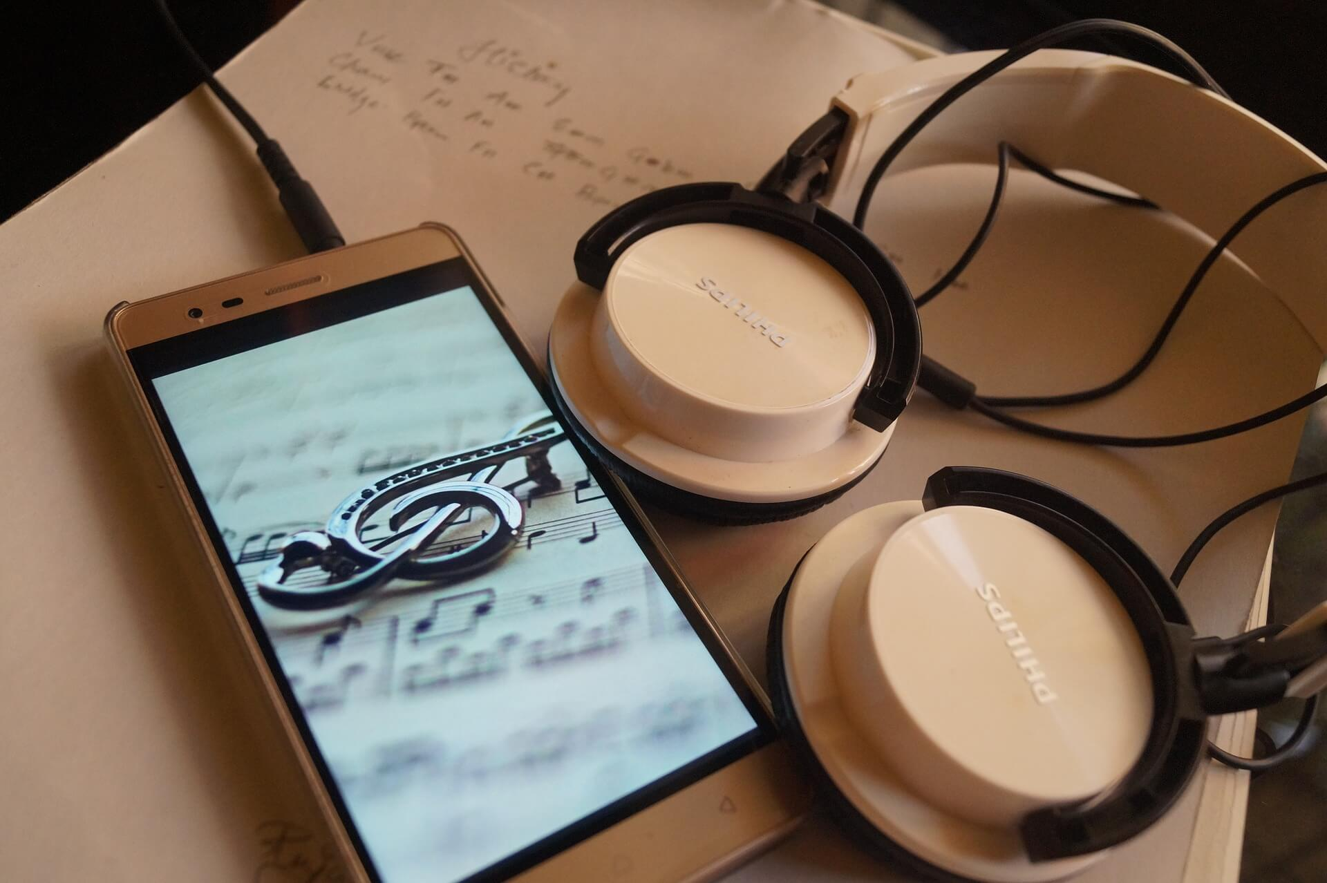 smartphone with violine key image and headphone on a table