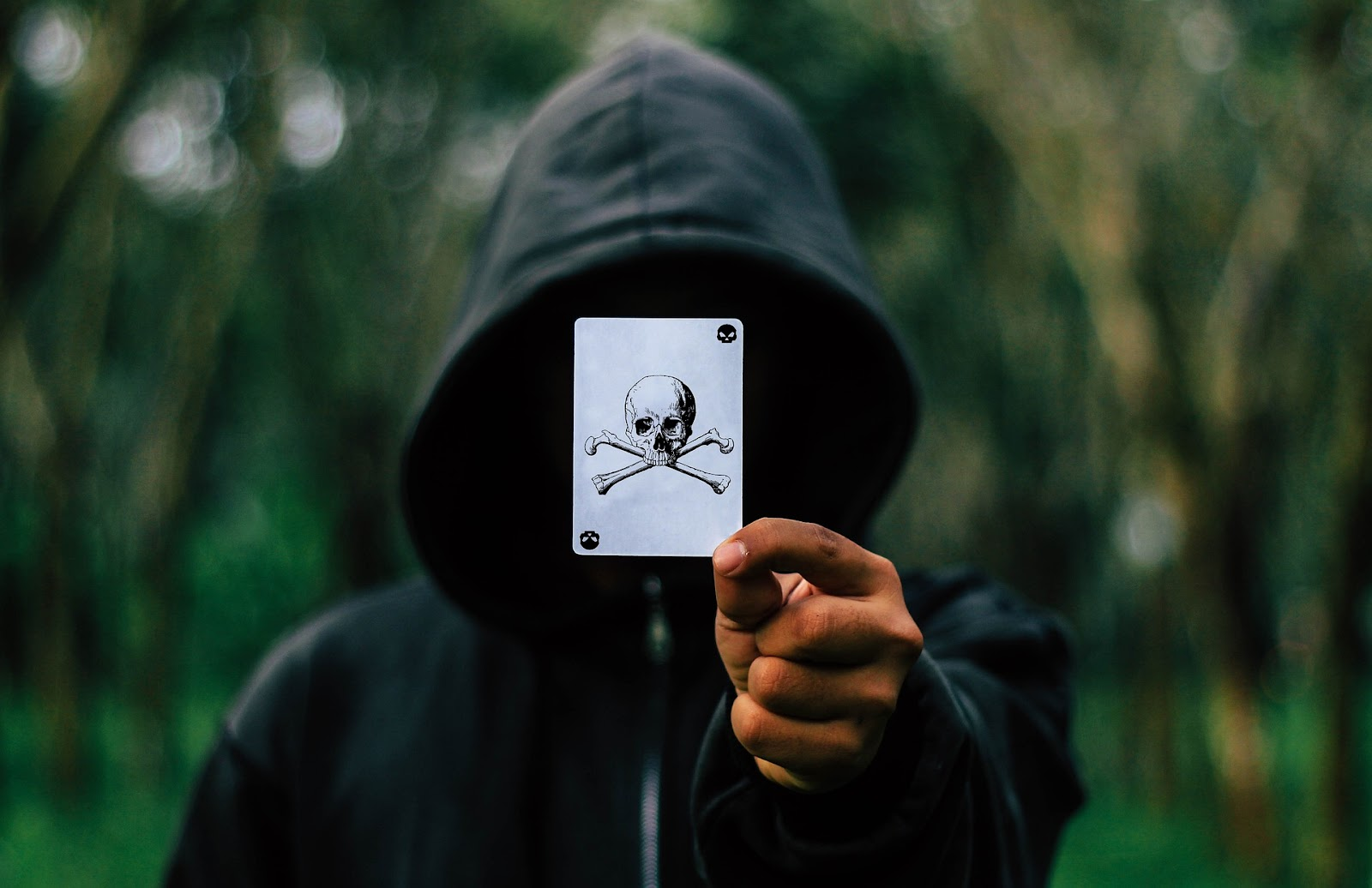 guy with face covered by a card with death symbol