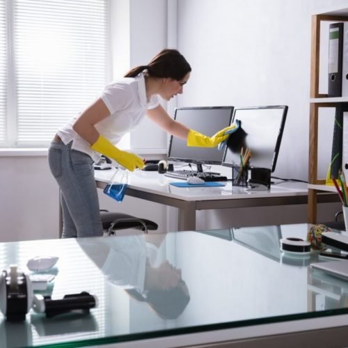 A woman carefully cleaning a screen.