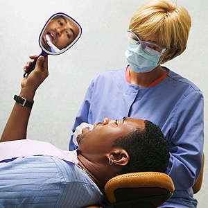 man having his teeth cleaned at a dentist office