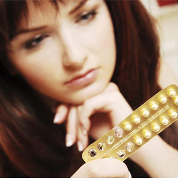 young girl looking at birth control medication
