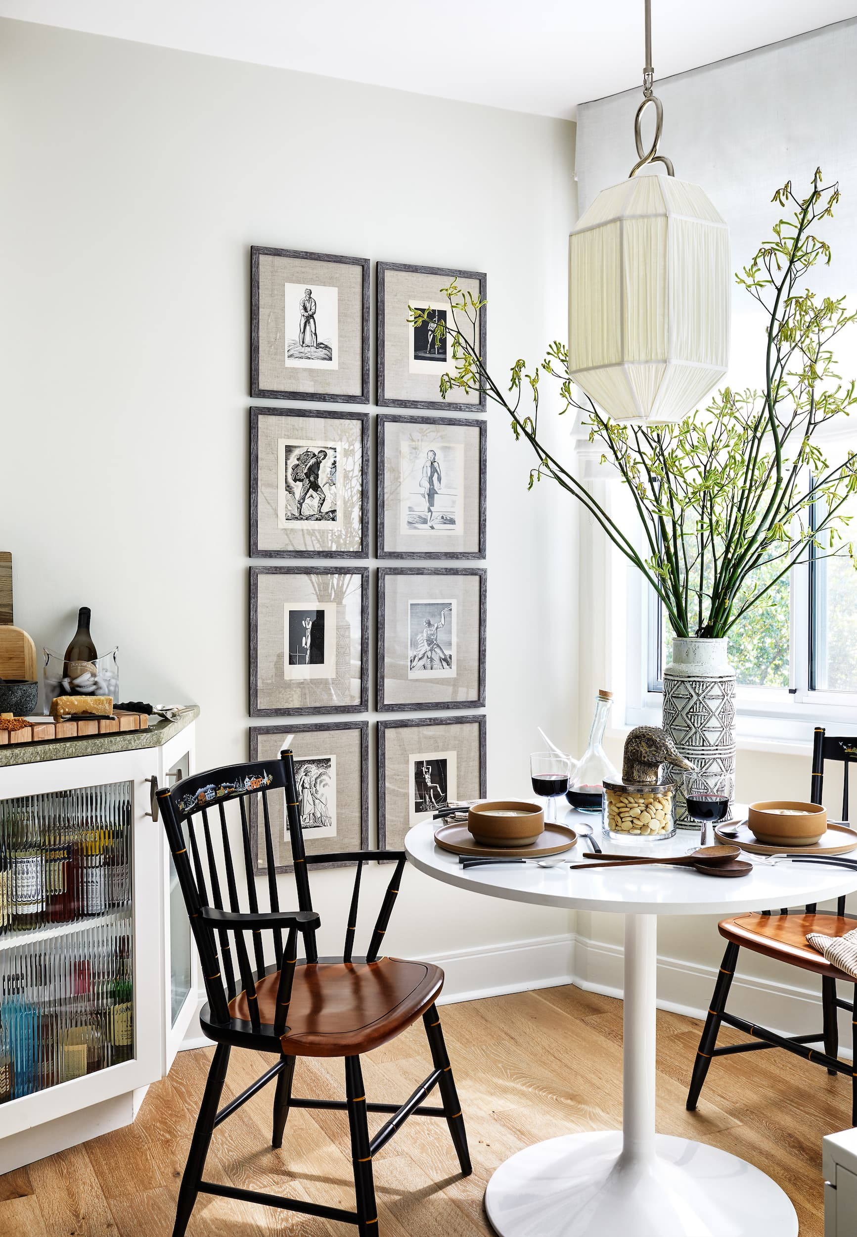 Kitchen table with two chairs and many antiques.