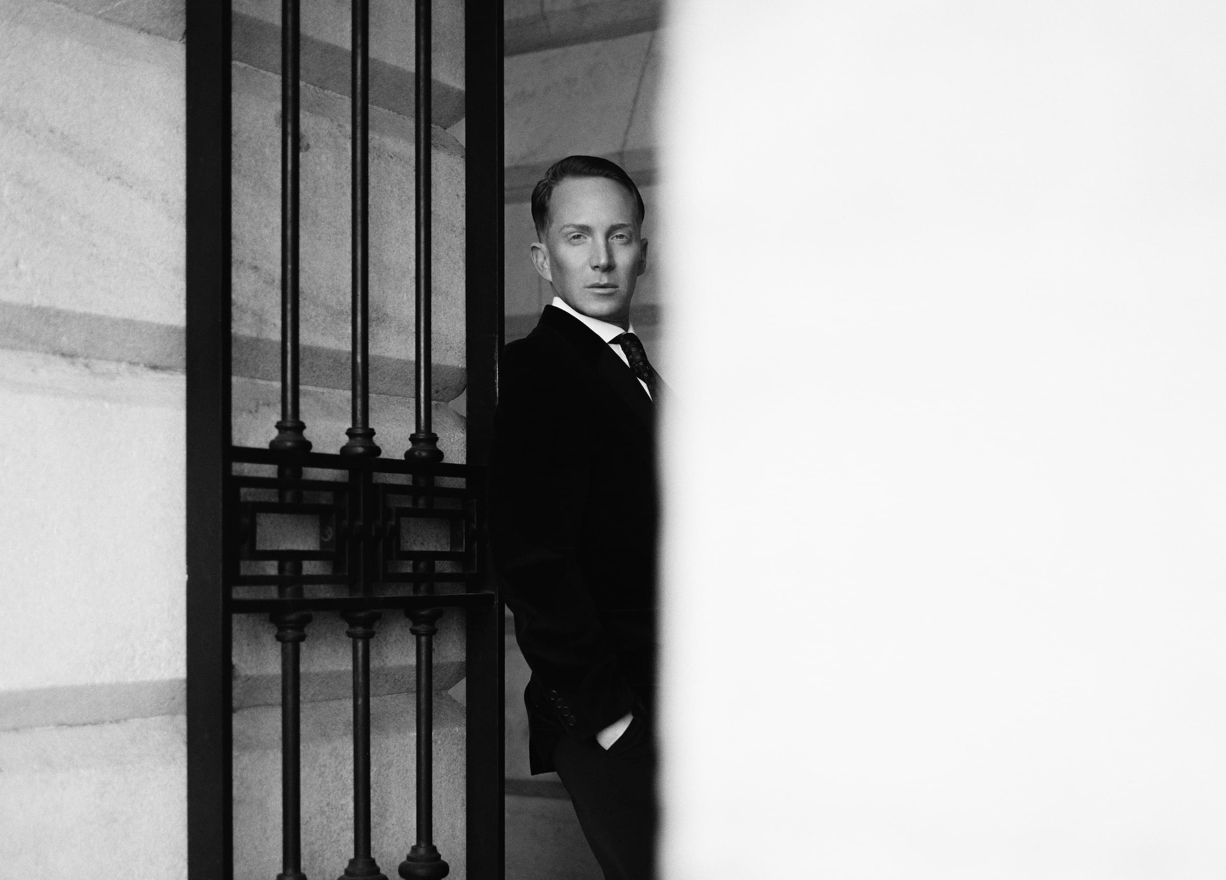 Partially obscured black and white portrait of Paul Corrie leaning on an iron gate.