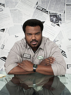 Craig Robinson as Daryl Philbin from the Office sitting at a table looking at the camera with articles posted on the wall behind him