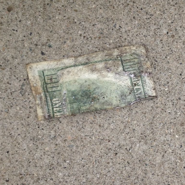 a tattered and worn out hundred dollar bill on the ground