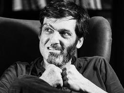 black and white image of dan ariely sitting in a recliner