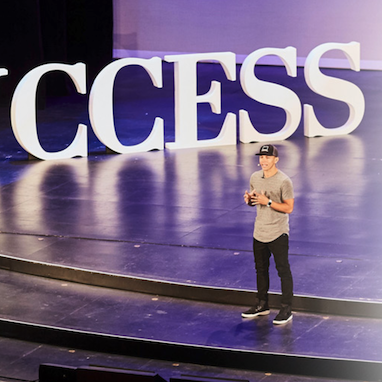"peter voogd giving a lecture in front of a backdrop of the word ""success"""