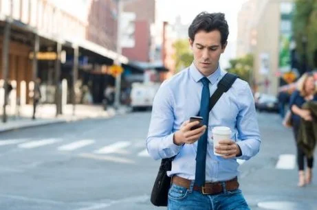 a man receiving a text message notifying him of training