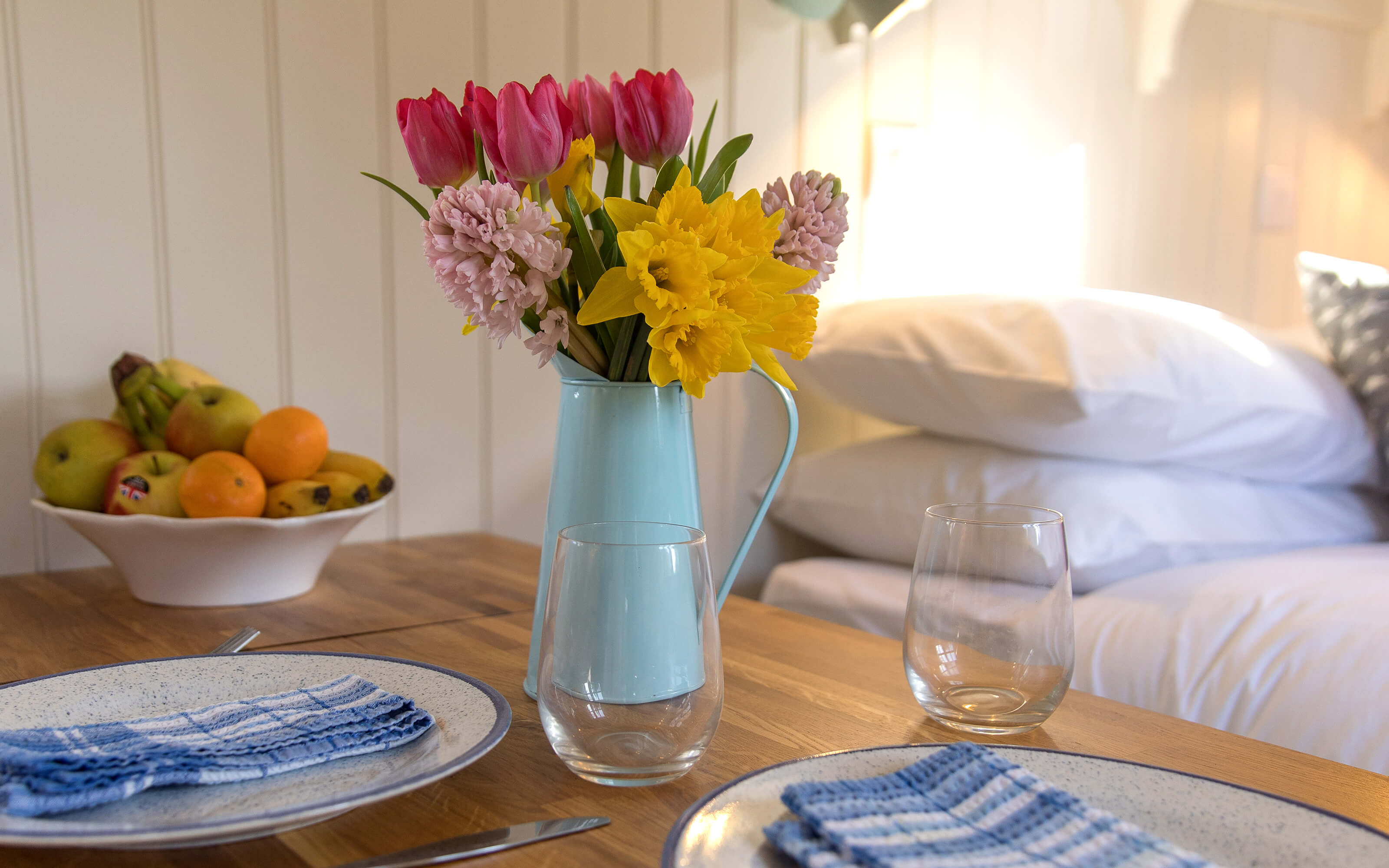 A table setting with flowers inside a shepherds hut.