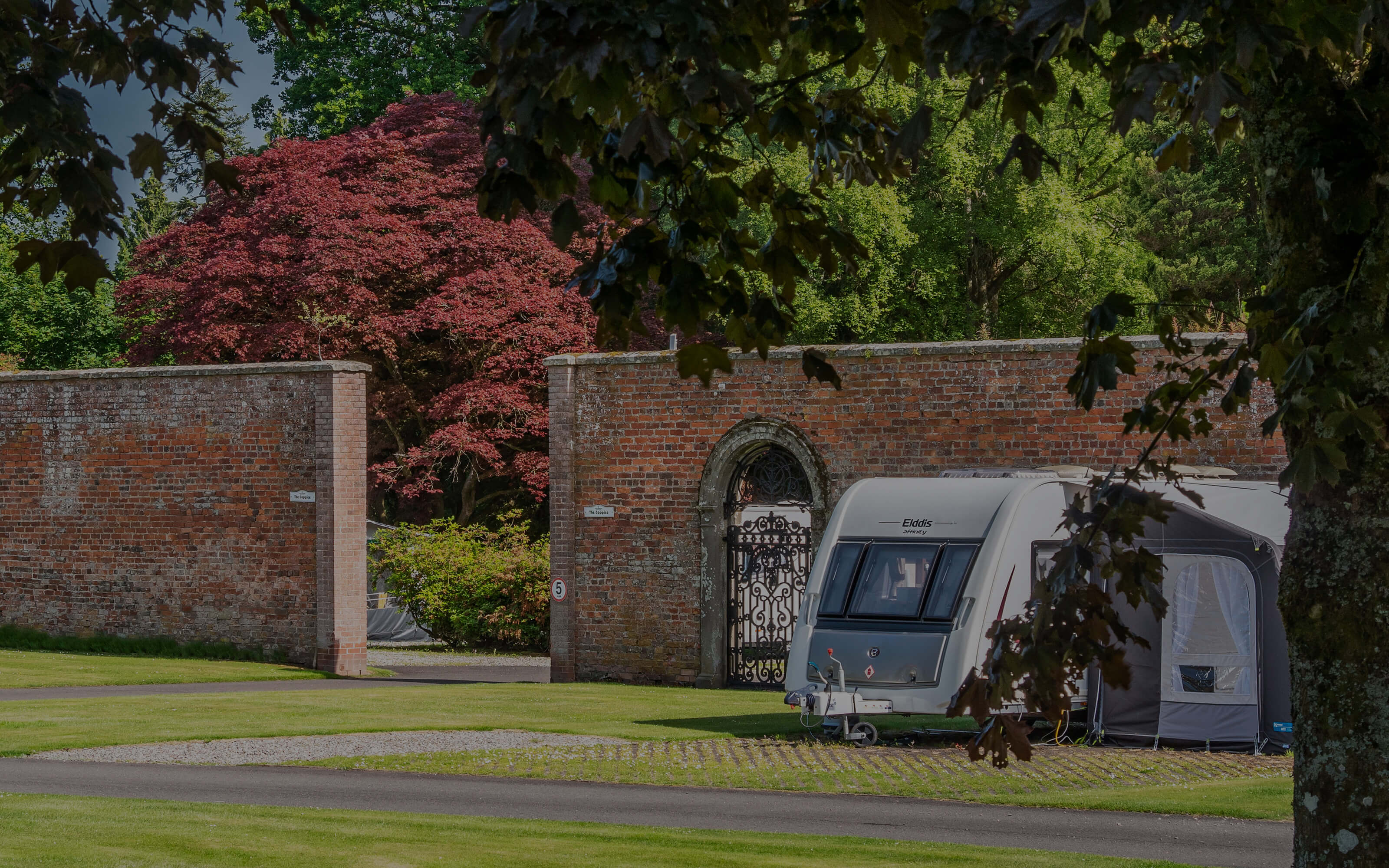 A caravan to the right of the walled garden entrance.