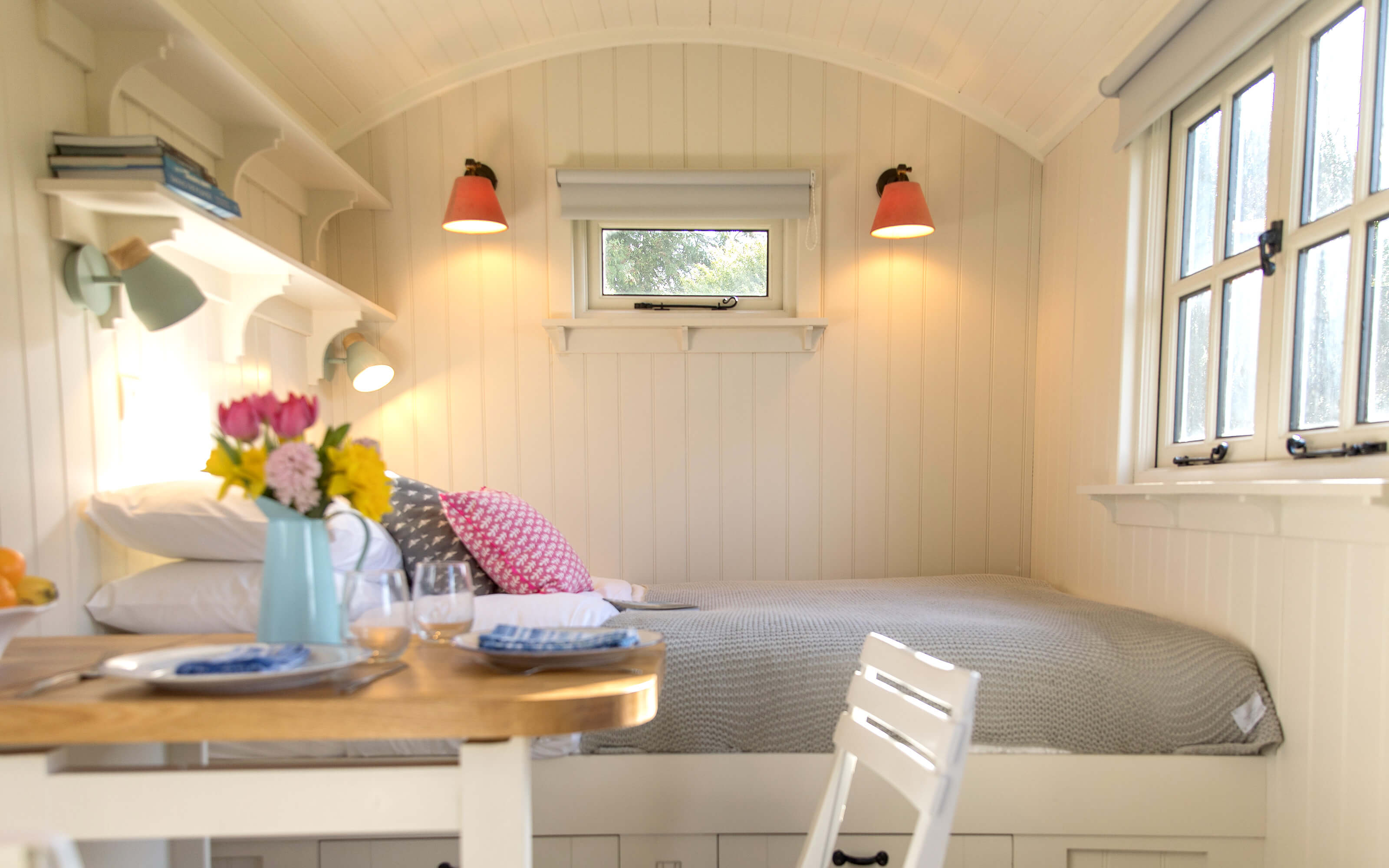 The king sized bed inside a shepherds hut.