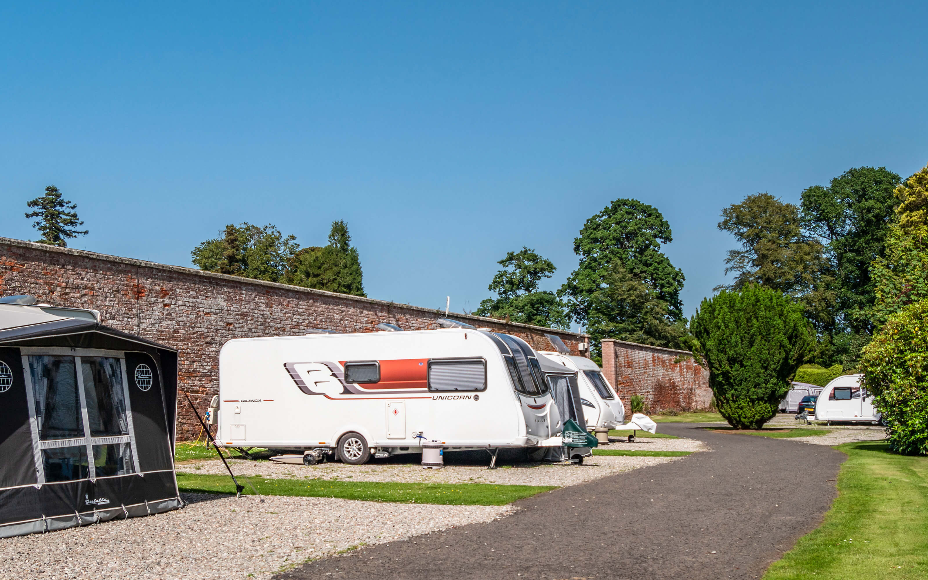 A tent and caravan on the outside wall of the walled garden.