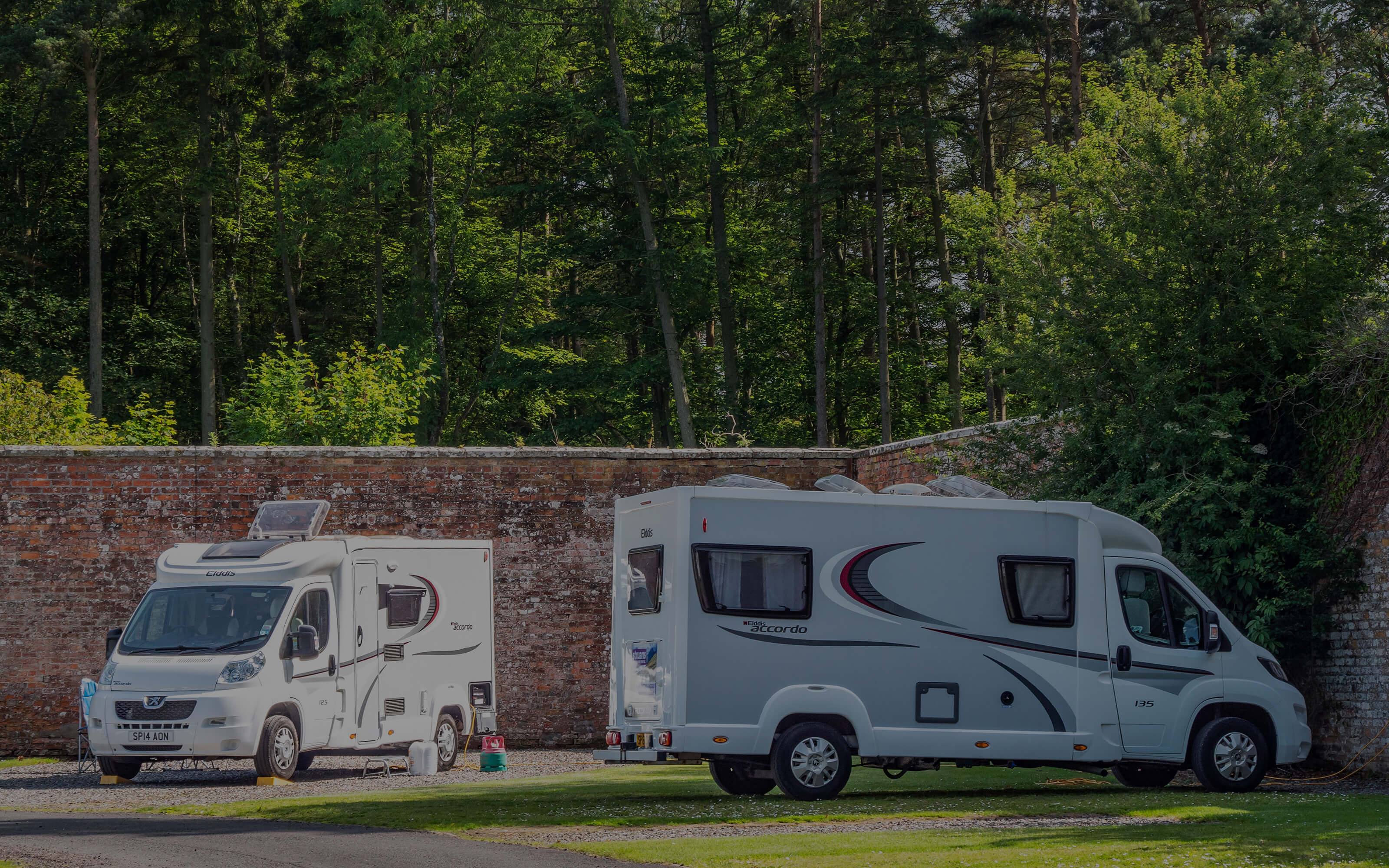 Two large motorhomes parked inside the walled garden.