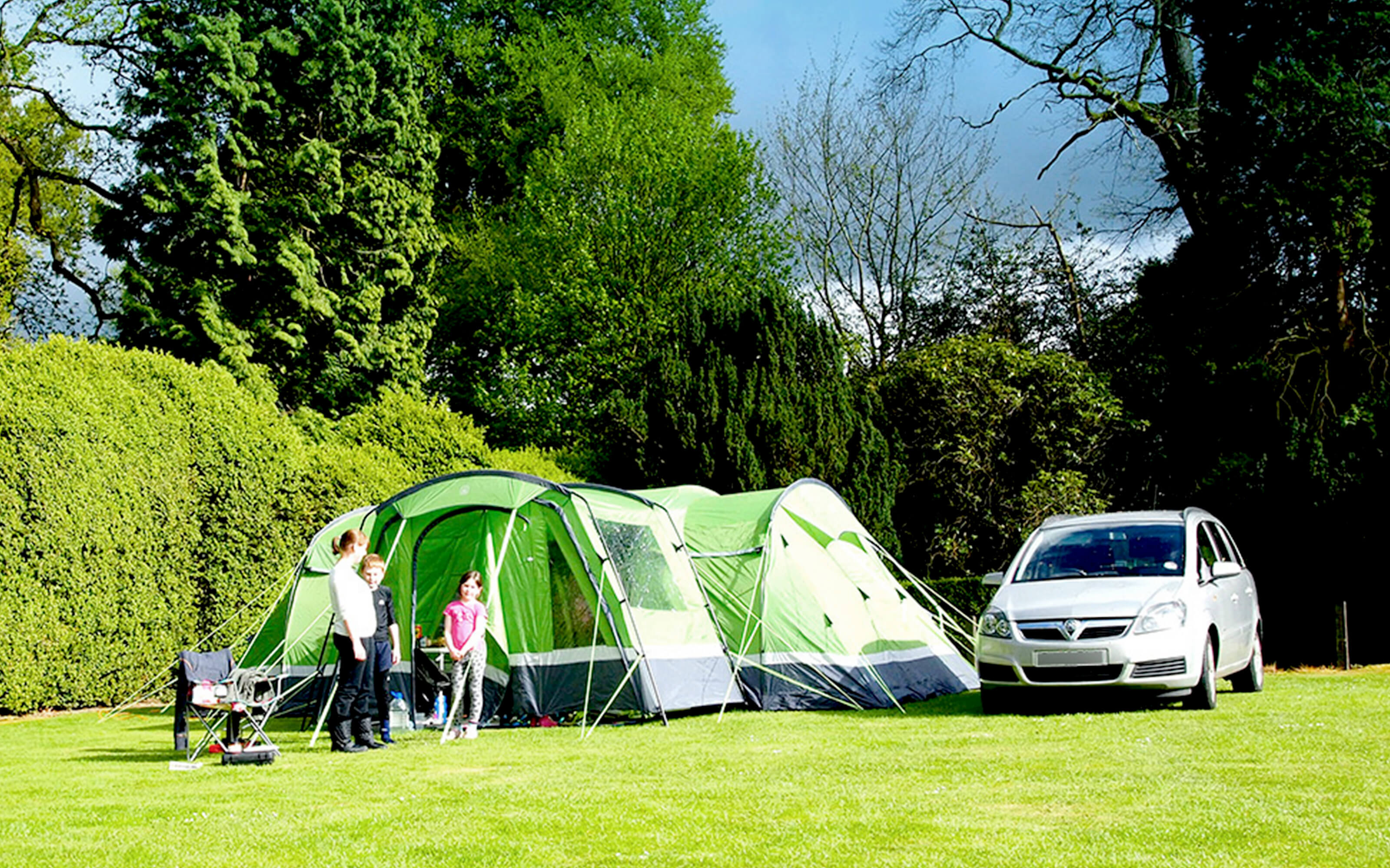 A family group setting up a large tent on a grass pitch.