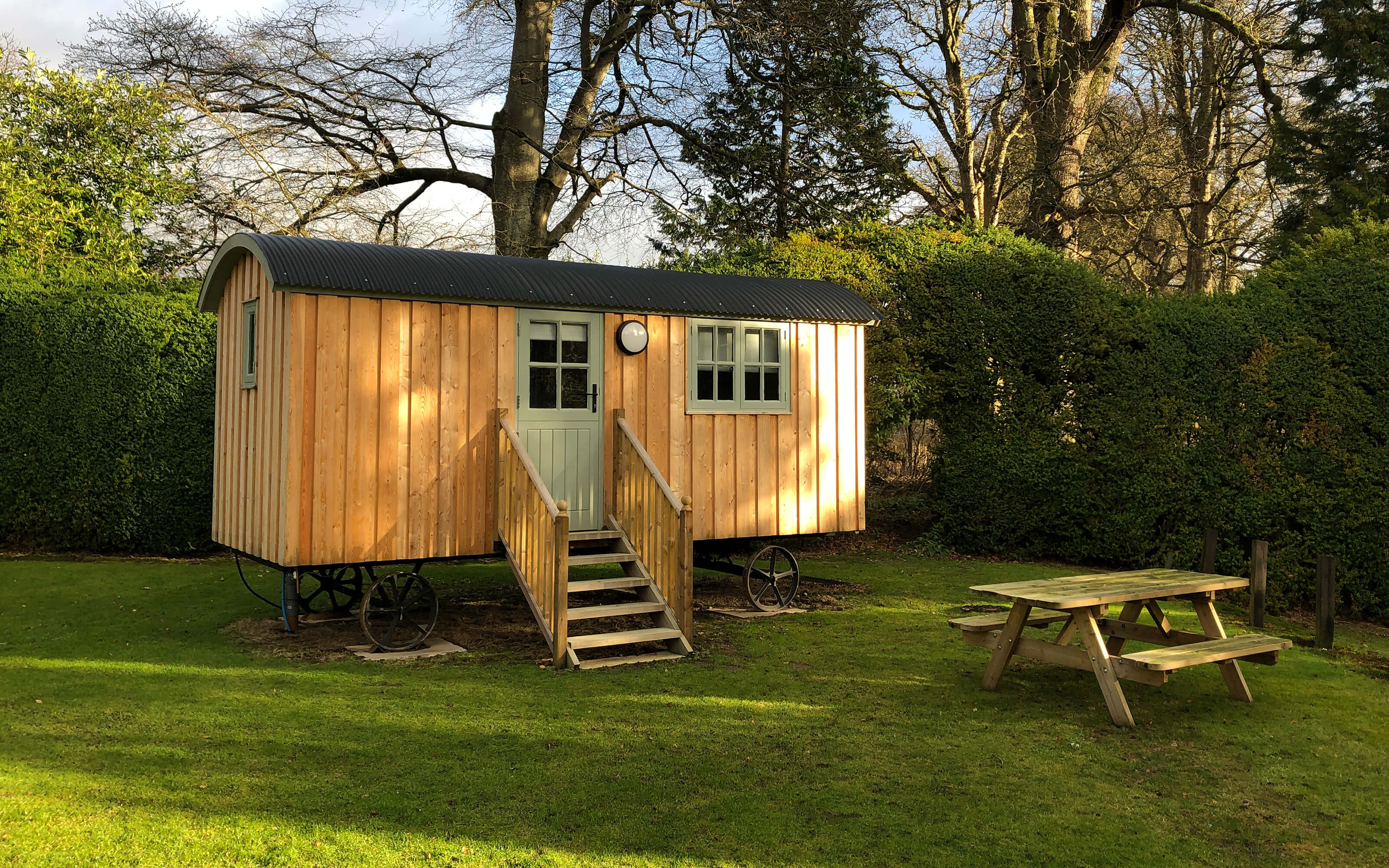 A secluded shepherds hut with a picnic table on the lawn.