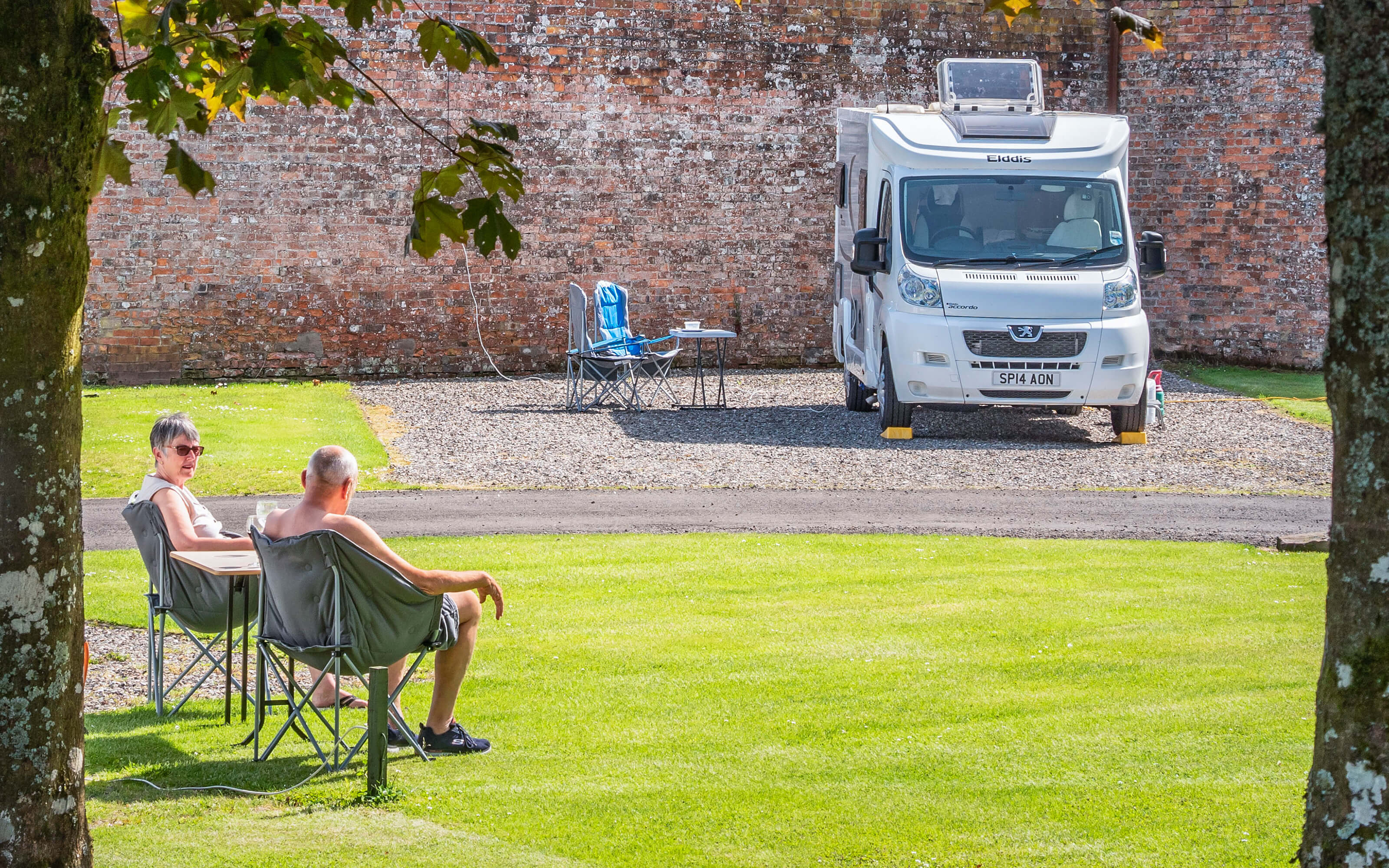 Guests sitting on garden chairs in the sun opposite their motorhome.