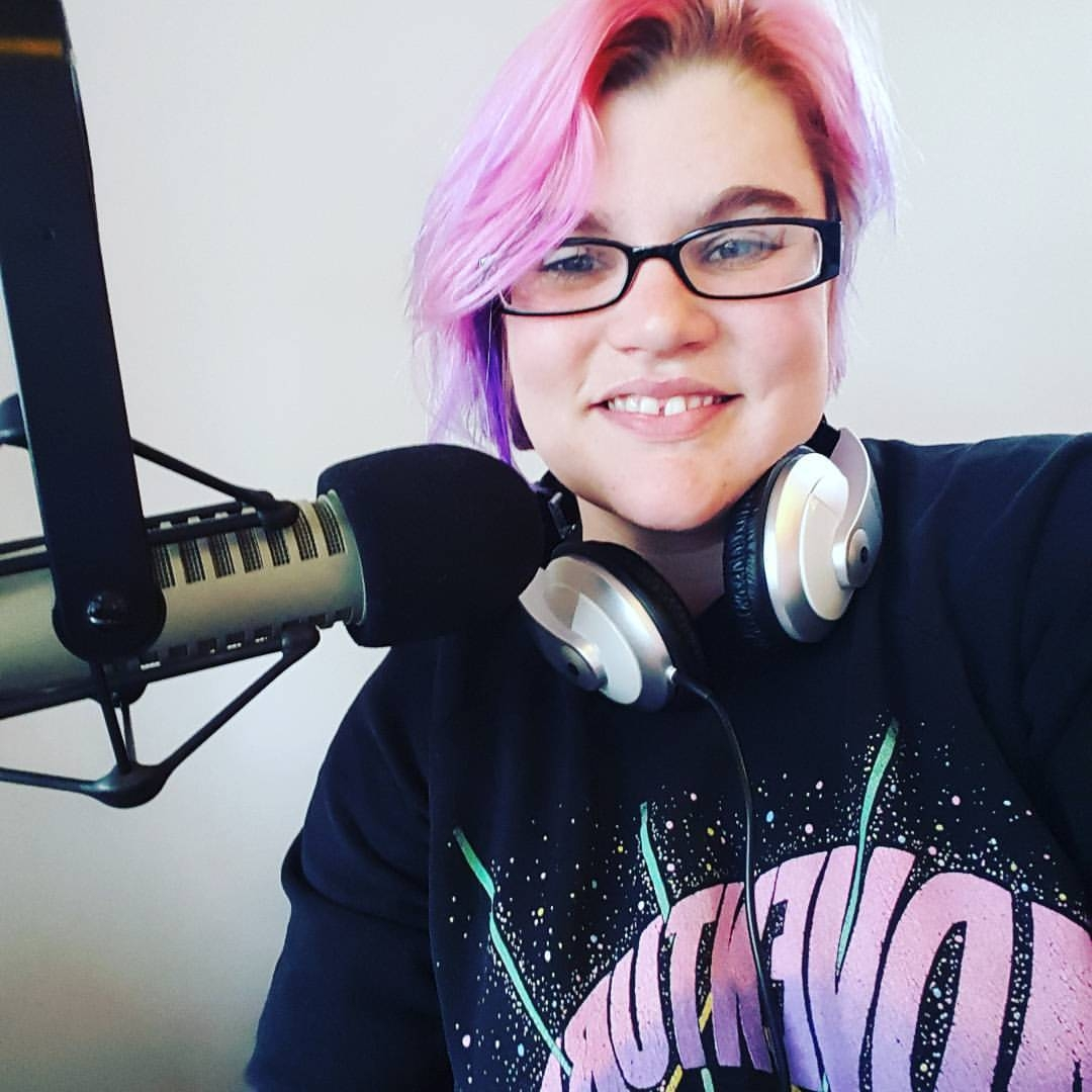 Woman with glasses wears headphones around neck and sits behind a broadcast microphone