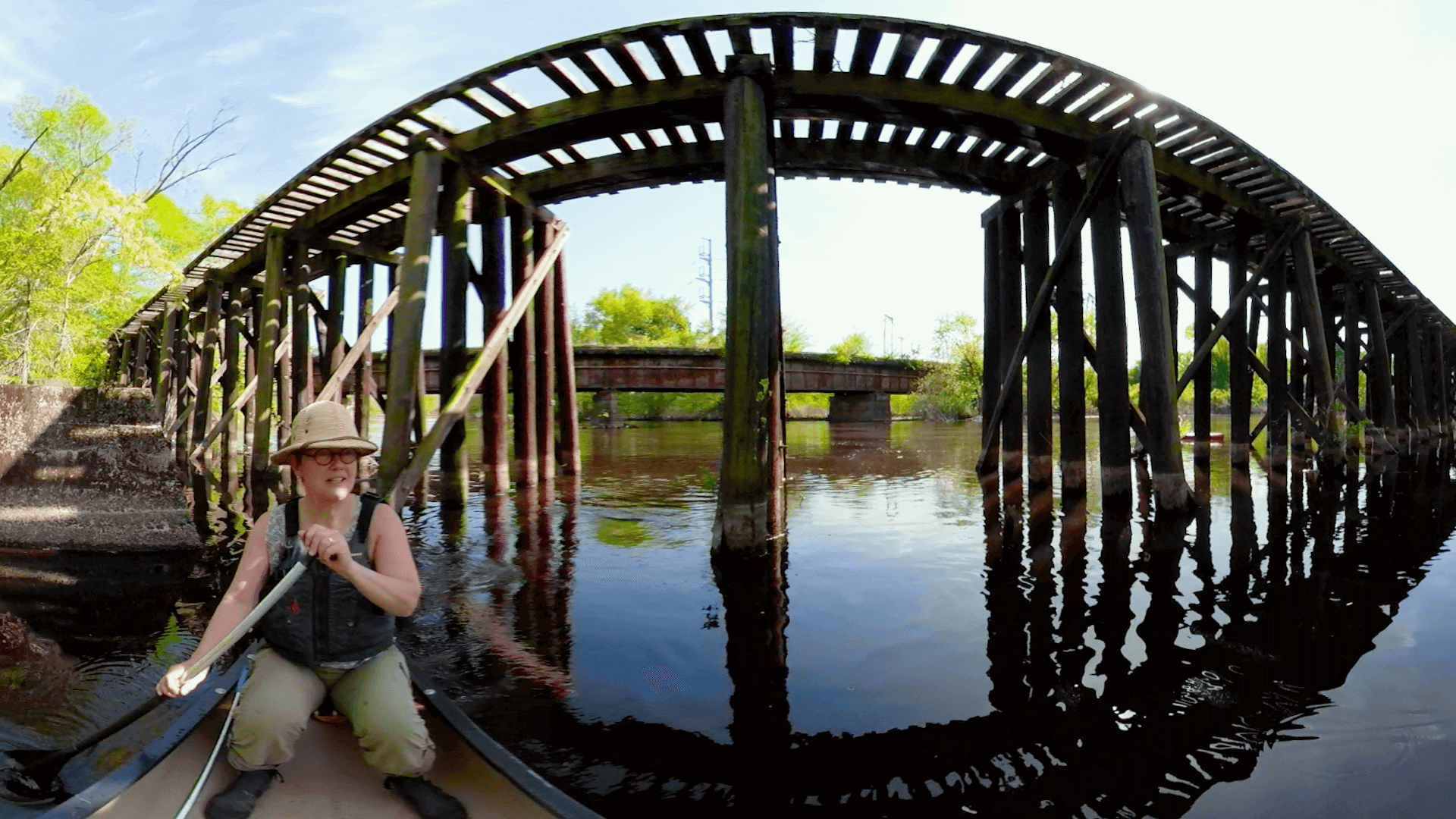 360 photo of a woman paddling in a canoe on the concord river by a bridge