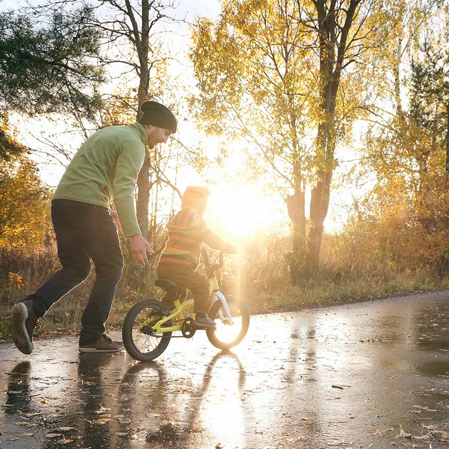 Father helping child ride bicycle