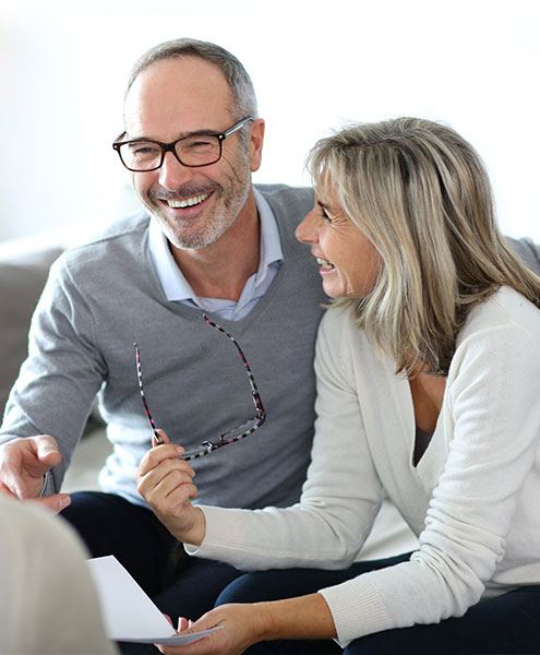 Middle aged couple discussing their will and estate planning, smiling at each other.