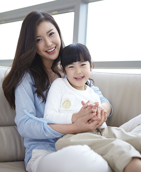Mom and her young child, smiling and sitting on the couch.