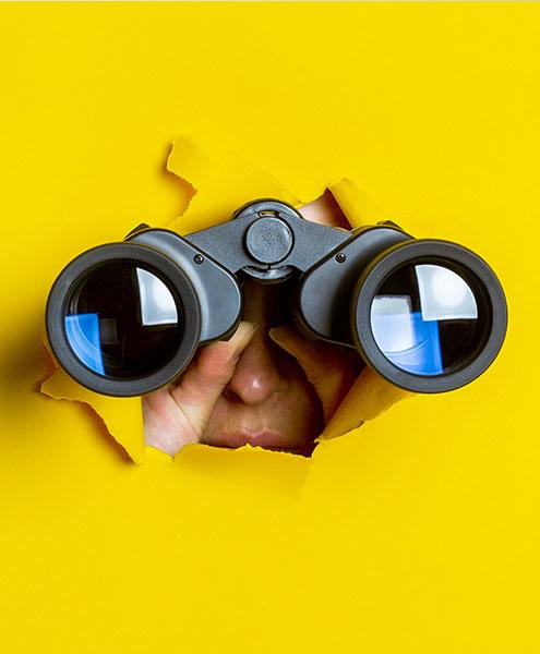 Pair of binoculars breaking through a yellow background
