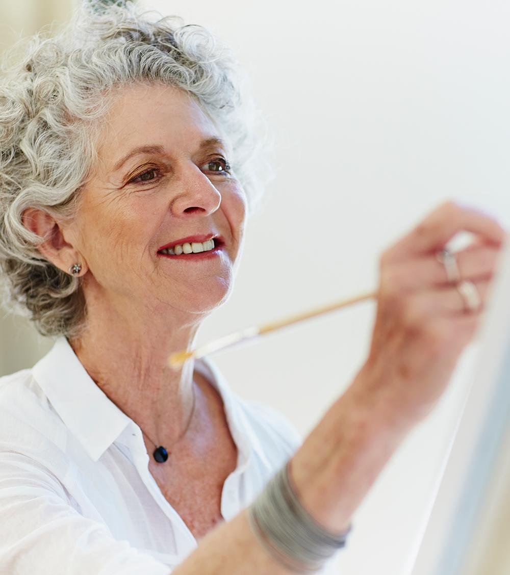 grauhaarige Frau vor Staffelei mit Pinsel inder Hand malt
