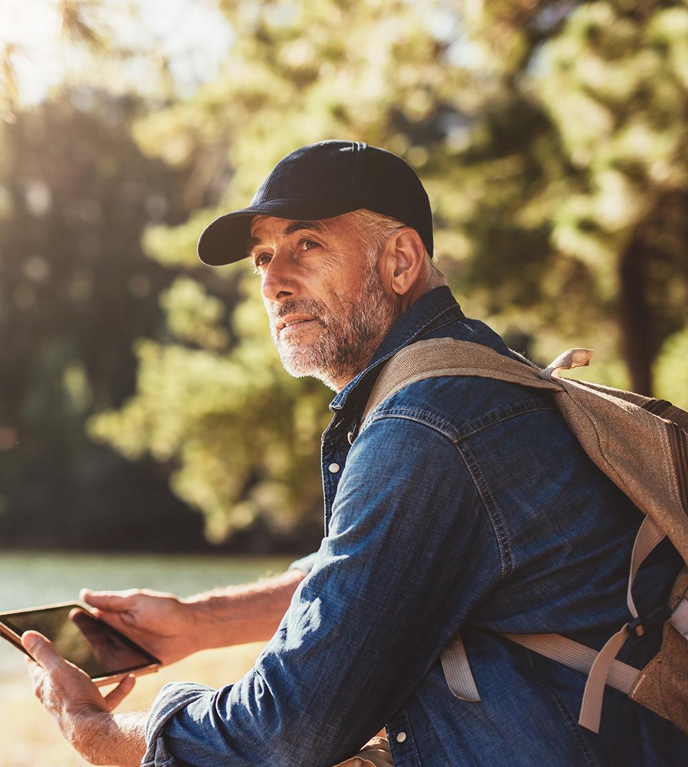 Mann mit Rucksack sitzt auf einer Parkbank