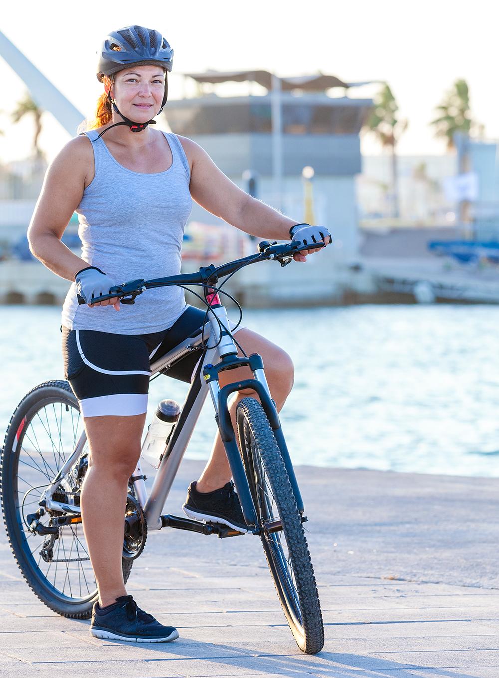 Grau in sportlichem Outfit sitzt auf einem Fahrrad und trägt einen Fahrradhelm