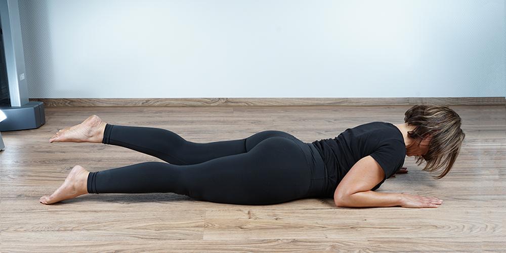 Frau im Beinheber auf dem Bauch