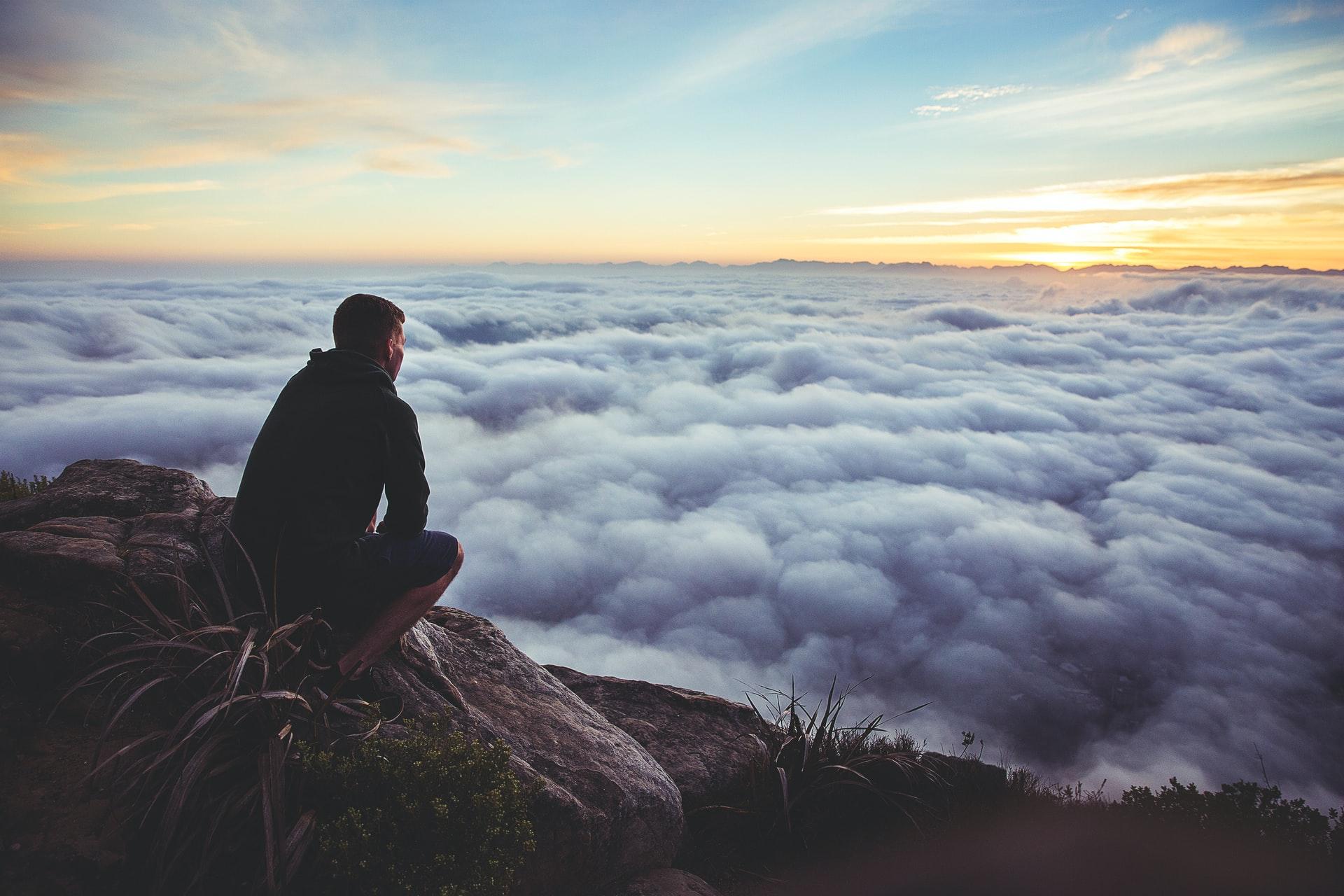Mann auf Berggipfel schaut über den Wolken in die Ferne