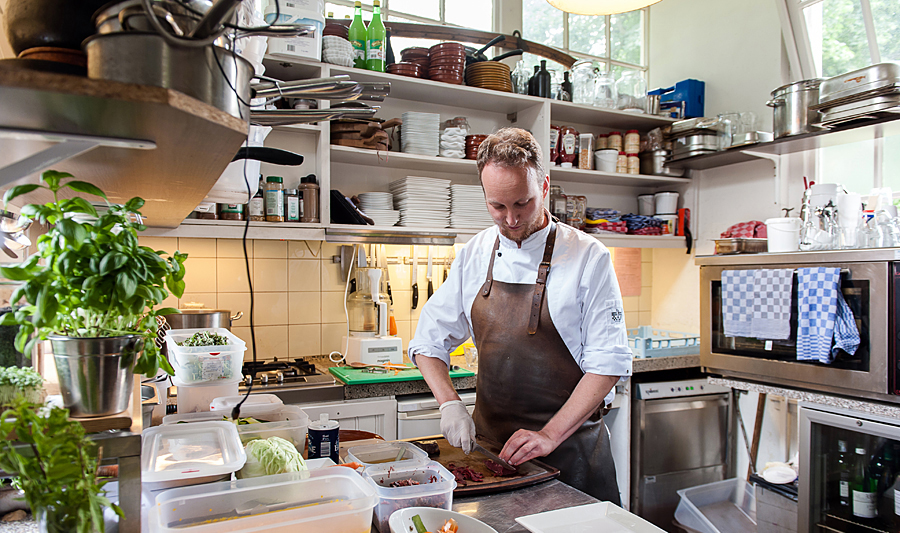 A chef in his kitchen working on a recipe