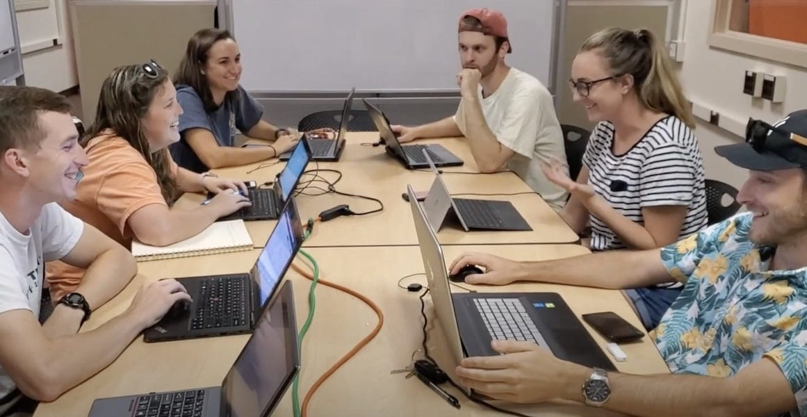 Students sitting with computers around a large table
