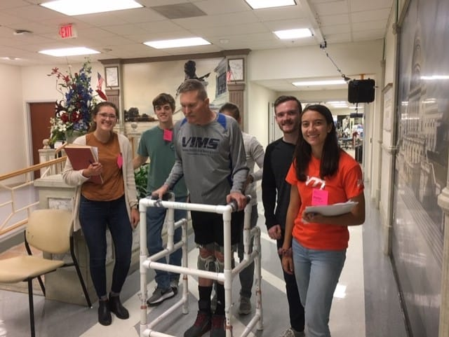 A group of students helps a man by building a walker