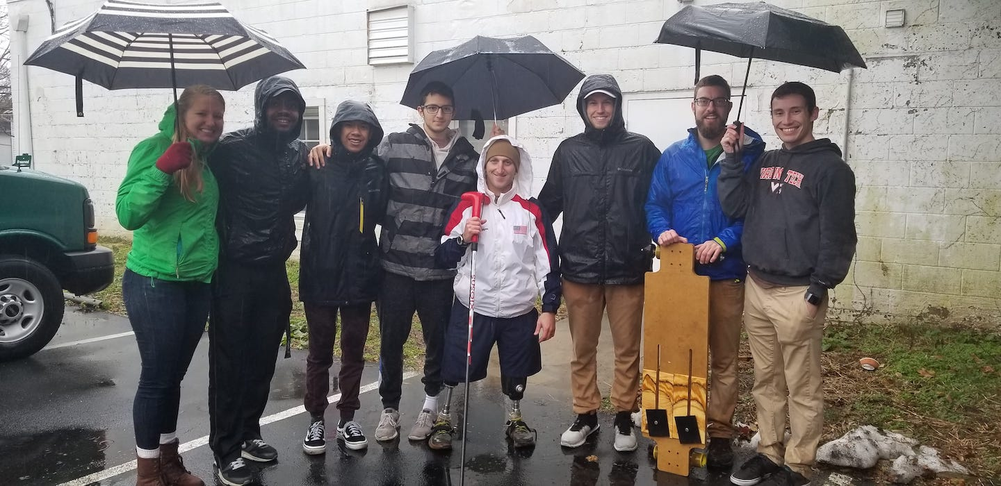 A group of students stand with a Challenger under umbrellas